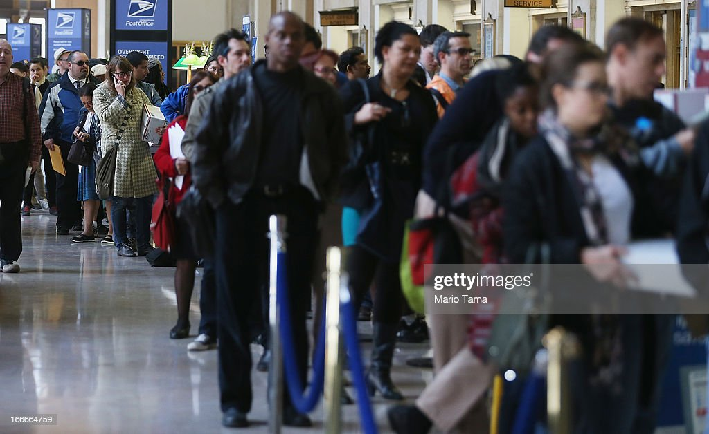 People wait in line inside the James A. Farley post office building April 15, 2013 in the Manhattan borough of New York City. With the U.S. tax deadline of midnight April 15 rapidly approaching, last-minute filers are filling up the nation's post offices.