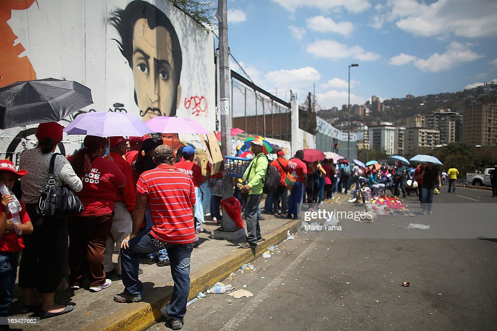 People wait in line more than a kilometer away to view the body of deceased Venezuelan President Hugo Chavez in front of a mural of Simon Bolivar on March 9, 2013 in Caracas, Venezuela. Venezuelans continue to wait in line for hours to pay their last respects to Chavez on the day after his funeral. Venezuela's elections commission has set April 14 as the date for voting to replace the late Chavez.