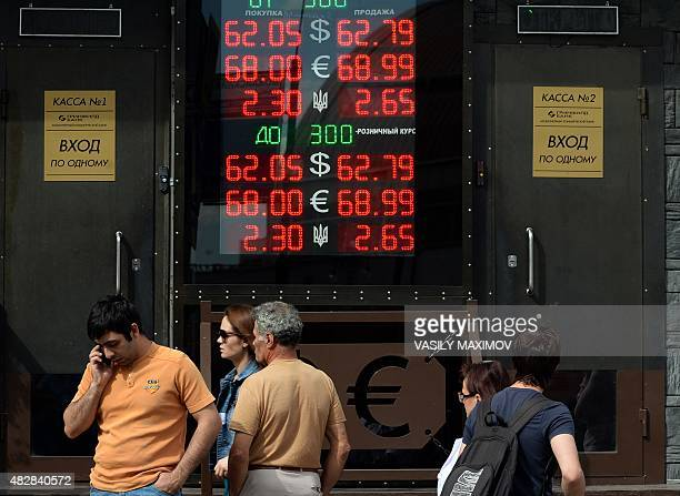 People wait in line next to a board listing foreign currency rates in comparison with the Russian ruble outside an exchange office in Moscow on...