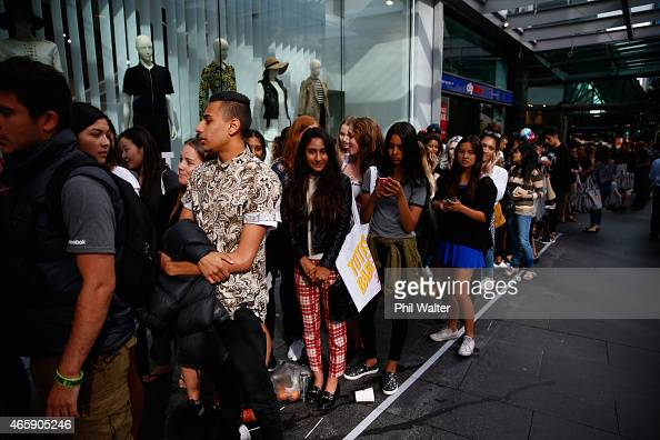 People wait in line on Queen Street before the opening of New Zealand's first TopShop and TopMan store on March 12 2015 in Auckland New Zealand Fans...