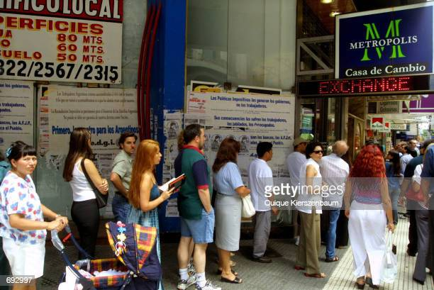 People wait in line outside a currency exchange house January 18 2002 in Buenos Aires Argentina The Central Bank intervened January 17 2002 in an...