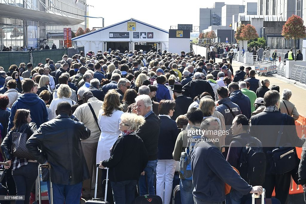 People wait in line outside the departure hall at Brussels Airport on the first day of its partly re-opening on May 2 2016, 40 days after suicide attacks claimed by the Islamic State group which killed 32 people, half of them at the air hub. / AFP / BELGA / ERIC LALMAND / Belgium OUT