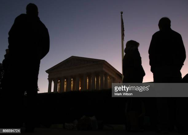 People wait in line to attend the fall session of the US Supreme Court on October 2 2017 in Washington DC The high court will hear several cases...