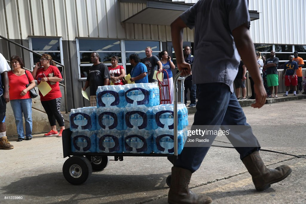 People wait in line to buy water at the Coastal Industrial and Specialty gas welding supplies store after the water supply to the city of Beaumont was shut down after Hurricane Harvey passed through on August 31, 2017 in Beaumont, Texas. Harvey, which made landfall north of Corpus Christi August 25, has dumped more than 50 inches of rain in some areas in and around Houston.