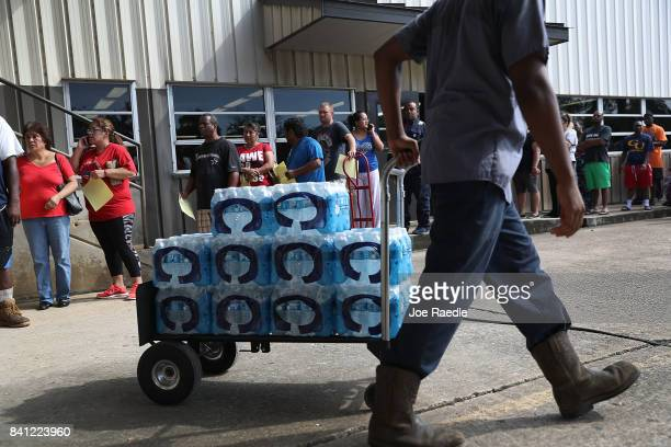 People wait in line to buy water at the Coastal Industrial and Specialty gas welding supplies store after the water supply to the city of Beaumont...