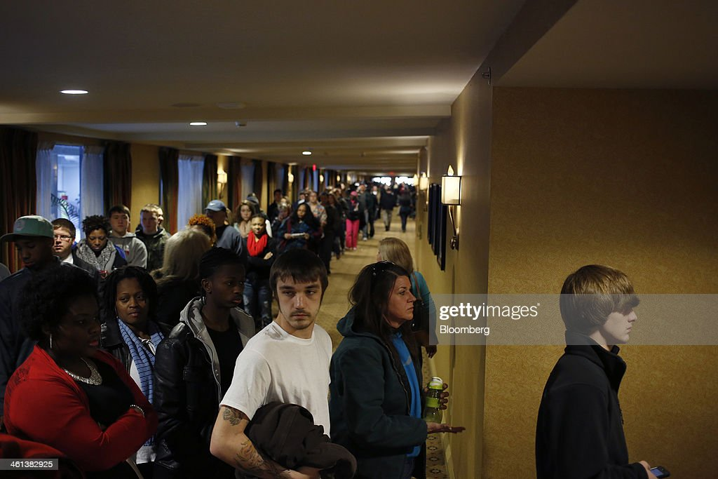 People wait in line to enter a job fair held by Kentucky Kingdom amusement park to hire seasonal summer workers in Louisville, Kentucky, U.S. on Saturday, Jan. 4, 2014. Companies added more workers than projected in December as U.S. employers grew more optimistic about the prospects for demand, a private report based on payrolls showed Jan. 8. Photographer: Luke Sharrett/Bloomberg via Getty Images