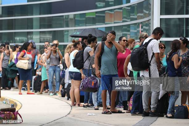 People wait in line to get a flight out of the Luis Munoz Marin International Airport as they try to return home or escape the conditions after...