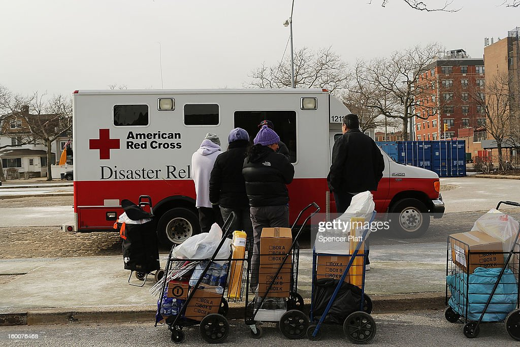 People wait in line to get food items from a Red Cross Disaster Relief truck in the Rockaways following Hurricane Sandy on January 25, 2013 in the Queens borough of New York City. Three months after Sandy devastated parts of New York and New Jersey, hundreds of residents are still without electricity and heat and depend on churches and charities to meet their basic needs. This past week saw some of the coldest temperatures of the winter hit parts of New York.