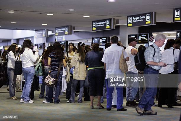 People wait in line to pass through the US Customs and Border Protection Passport control area as they arrive January 19 2007 at Miami International...