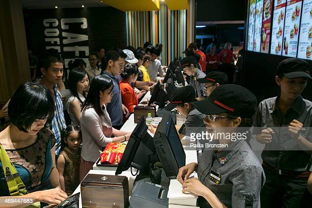 People wait in line to purchase food at the new McDonald's restaurant in Ho Chi Minh city February 14 2014 The first Mac Donald's in Vietnam opened...