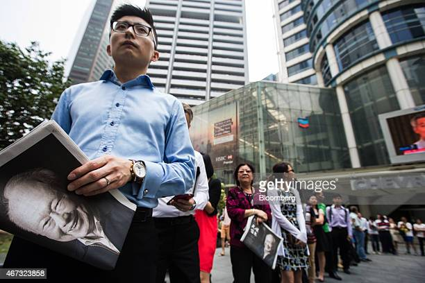 People wait in line to purchase special edition newspapers following the death of Singapore's first elected Prime Minister Lee Kuan Yew at Raffles...
