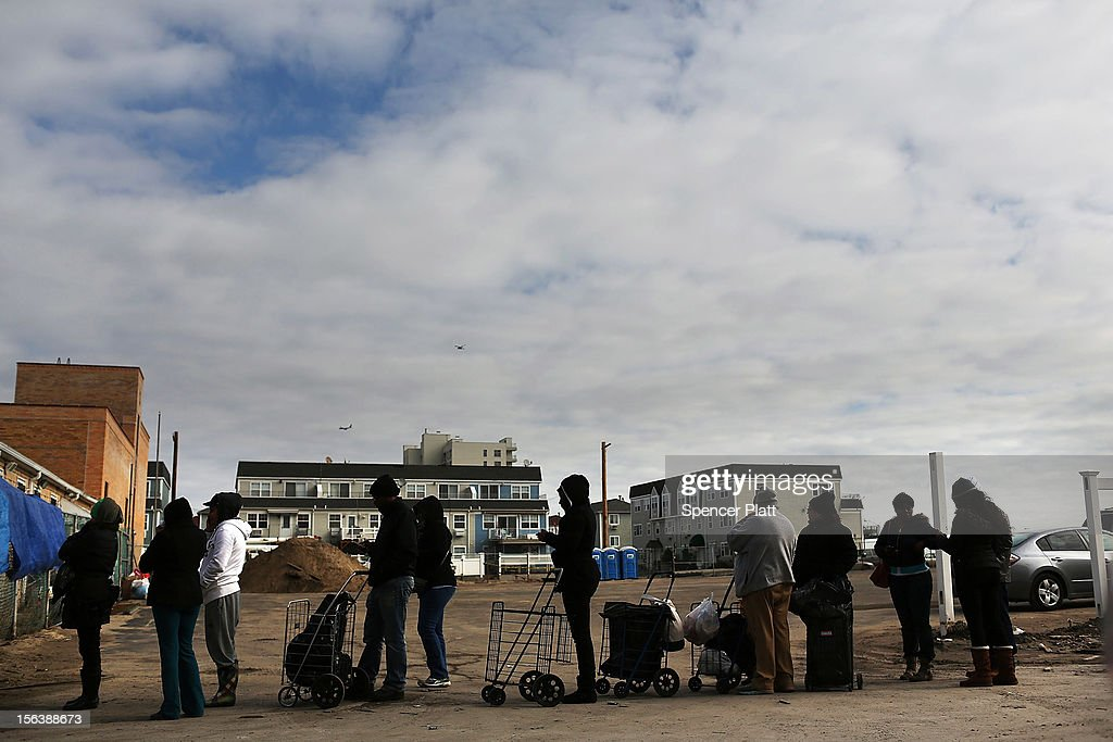 People wait in line to receive free food from a charity in the heavily damaged Rockaway neighborhood where a large section of the iconic boardwalk was washed away on November 14, 2012 in the Queens borough of New York City. Two weeks after Superstorm Sandy slammed into parts of New York and New Jersey, thousands are still without power and heat.