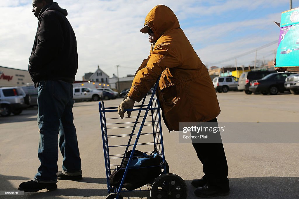 People wait in line to receive free food from the American Red Cross in the heavily damaged Rockaway neighborhood where a large section of the iconic boardwalk was washed away on November 14, 2012 in the Queens borough of New York City. Two weeks after Superstorm Sandy slammed into parts of New York and New Jersey, thousands are still without power and heat.
