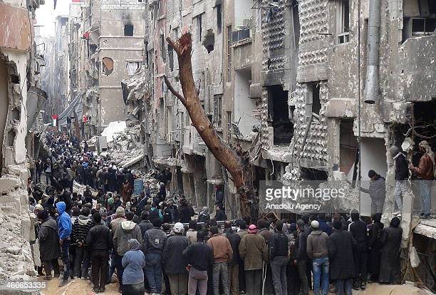 People wait in line to receive the humanitarian aid delivered by United Nations Relief and Works Agency for Palestine Refugees in the Near East and...