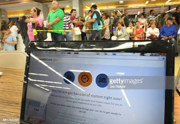 People wait in line to see an agent from Sunshine Life and Health Advisors as the Affordable Care Act website is reading 'HealthCaregov has a lot of...