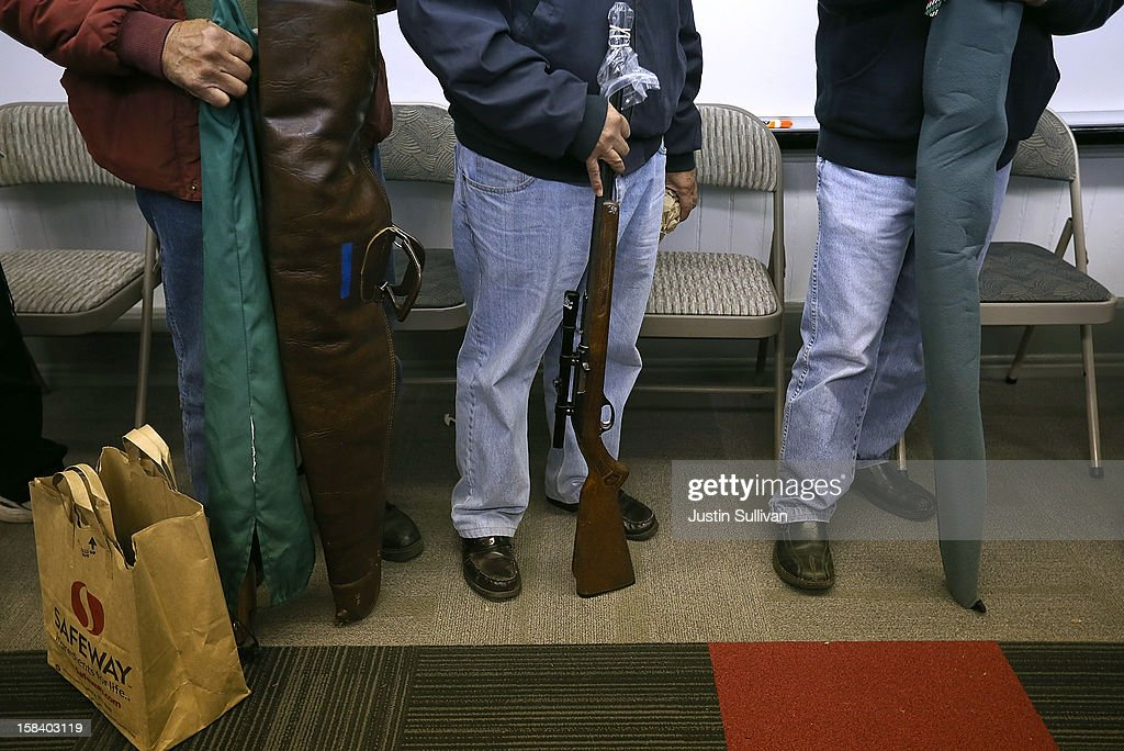 People wait in line to turn in firearms during a gun buy back program on December 15, 2012 in San Francisco, California. The San Francisco police department held a one-day gun buy back event that paid $200 per gun turned in. A better than expected crowd resulted in payback money running out and vouchers were issued to collect money within a week. Over 200 guns were collected.