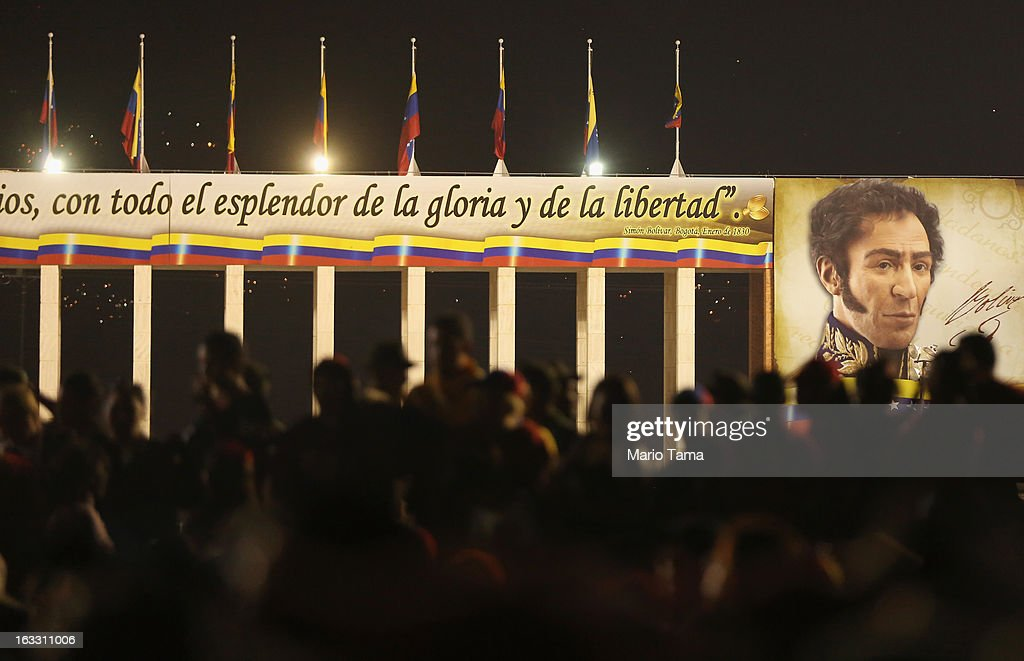 People wait in line to view the remains of late Venezuelan President Hugo Chavez beneath a portrait of Simon Bolivar outside the Military Academy on March 7, 2013 in Caracas, Venezuela. Countless Venezuelans waited on a mile-long line to pay their last respects to Chavez before his funeral tomorrow.