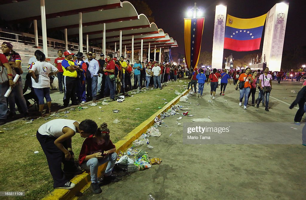 People wait in line (L) to view the remains of late Venezuelan President Hugo Chavez as others gather outside the Military Academy on March 7, 2013 in Caracas, Venezuela. Countless Venezuelans waited on a mile-long line to pay their last respects to Chavez before his funeral tomorrow.