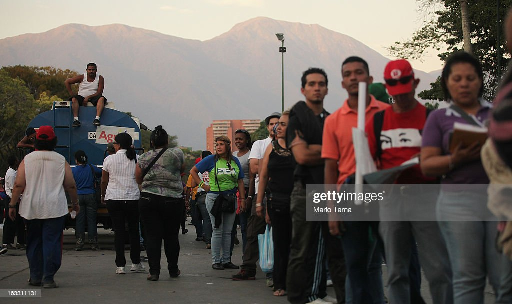People wait in line (R) to view the remains of late Venezuelan President Hugo Chavez as others gather outside the Military Academy on March 7, 2013 in Caracas, Venezuela. Countless Venezuelans waited on a mile-long line to pay their last respects to Chavez before his funeral tomorrow.