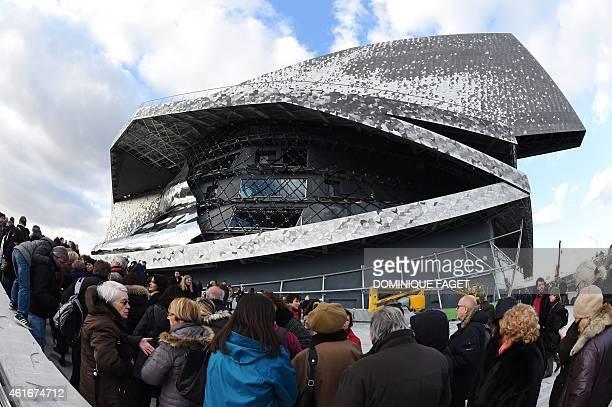 People wait in line to visit the new 'Philharmonie de Paris' in the Parc de la Villette near Porte de Pantin in northeastern Paris during open house...