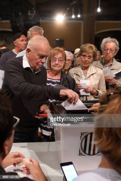 People wait in line to vote as a man casts his ballot in the referendum at Escola Industrial of Barcelona school polling station on October 1 2017 in...