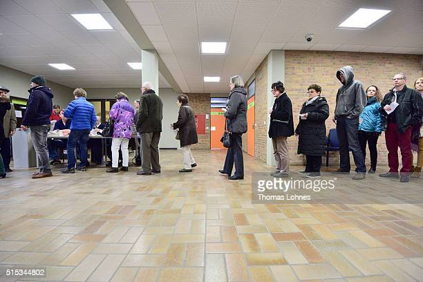 People wait in line to vote for the RhinelandPalatinate state elections at a polling station on March 13 2016 in Bad Kreuznach Germany State...