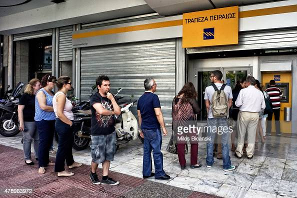 People wait in line to withdraw 60 euros from an ATM after Greece closed its banks on June 29 2015 in Athens Greece Greece closed its banks and...
