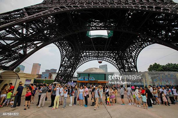 People wait in line under the 108 meter miniature of the Paris' Eiffel Tower to buy tickets in the theme park 'Window Of The World' in Shenzhen...