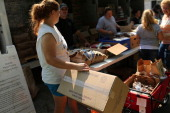 People wait in line with boxes to carry food during a food distribution by the Food Bank of the Southern Tier Mobile Food Pantry on June 20 2012 in...
