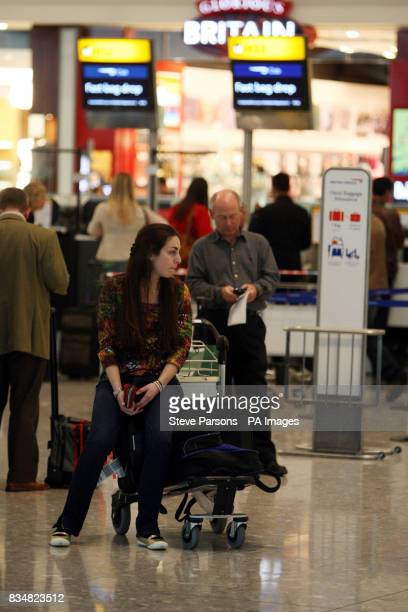 People wait in Terminal 5 of Heathrow Airport London after a glitch in the air traffic control system caused scores of flights to be cancelled or...
