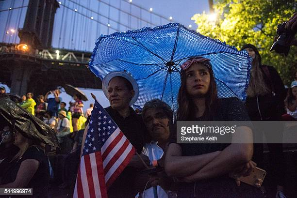People wait in the rain for the Macy's Fourth of July Fireworks from Brooklyn Bridge Park on July 4 2016 in the Brooklyn borough of New York City The...