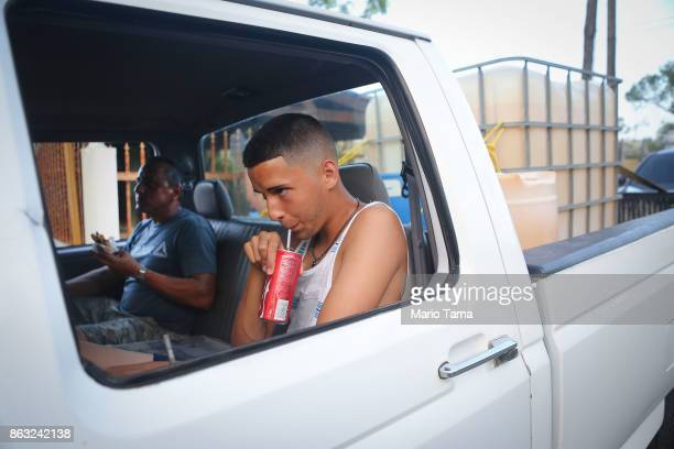 People wait in their truck to collect water with a pizza and sodas and a large water container at back nearly one month after Hurricane Maria struck...