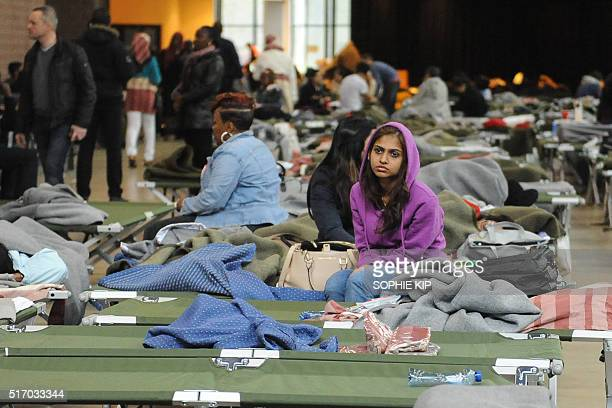TOPSHOT People wait inside a sport complex turned into a crisis facility for passengers in transit following the evacuation of Brussels airport on...