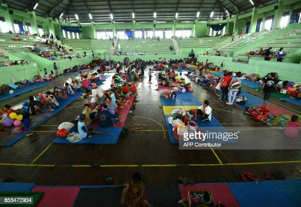 People wait inside an evacuation centre in Klungkung regency on the Indonesian resort island of Bali on September 25 2017 Authorities have raised...
