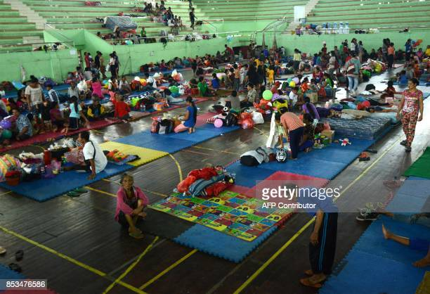 People wait inside an evacuation centre in Klungkung regency on the Indonesian resort island of Bali on September 25 2017 Nearly 50000 people have...