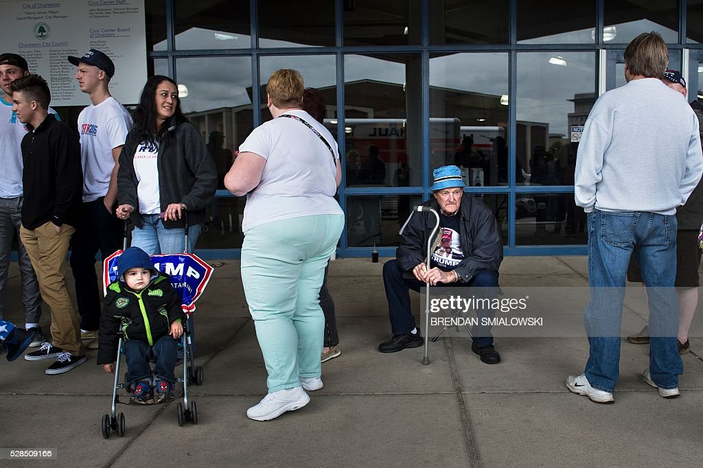 People wait line for a rally for Republican US Presidential hopeful Donald Trump in Charleston, West Virginia on May 5, 2016. It's the paradox of the 2016 US presidential elections: Hillary Clinton and Donald Trump are virtually assured of facing off against each other in November, and yet both are widely unpopular. / AFP / Brendan Smialowski