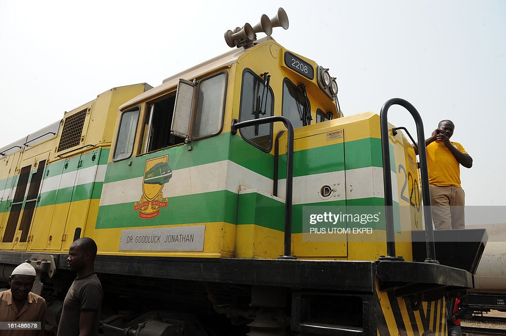 People wait next to a locomotive of the Nigerian Railway Corporation dedicated to President Goodluck Jonathan on February 8, 2013. The rejuvenated Nigerian Railway Corporation has resumed passenger and haulage services on the Lagos-Kano route following the refurbishing of engines and coaches over 20 years the corporation had gone bankrupt. Earlier last year, the corporation had acquired 20 pressurised tank wagons in preparation for the haulage of petroleum products from Lagos to northern parts of the country. The 20 wagons have the capacity to lift 900,000 litres of petroleum products, the equivalent of 27 road tankers.
