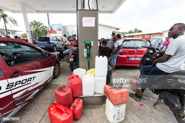 People wait next to cars at an outoffuel petrol station which handed out numbered coupons in order to organise distribution of a future resupply on...