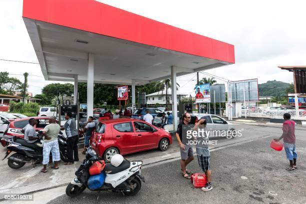 People wait next to vehicles at an outoffuel petrol station which handed out numbered coupons in order to organise distribution of a future resupply...