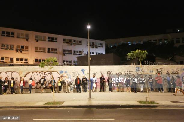 People wait on line for a bus at the end of the work day on May 12 2017 in Rio de Janeiro Brazil Today marked one year since President Michel Temer...