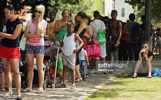 People wait on line to enter on opening day of the newly renovated McCarren Park Pool on June 28 2012 in the Brooklyn borough of New York City The...