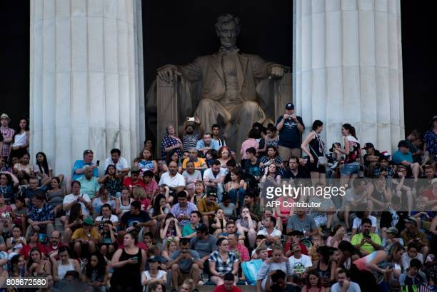 TOPSHOT People wait on the Lincoln Memorial for fireworks to celebrate US independence day on July 4 2017 in Washington DC / AFP PHOTO / Brendan...