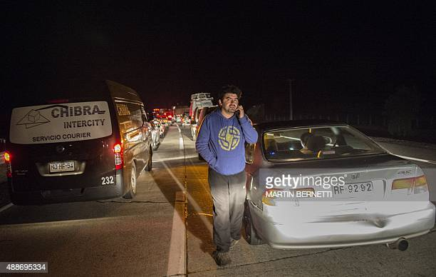 People wait on the Panamericana highway after a strong quake in Los Vilos some 150 km north of Santiago on September 17 2015 A strong 84magnitude...