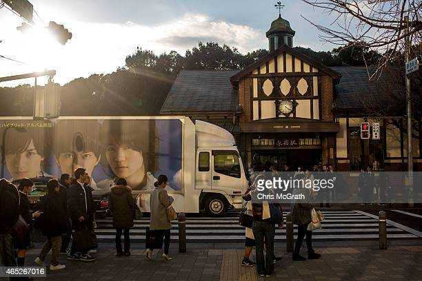 People wait on the sidewalk as a Japanese advertising truck is driven past the Harajuku train station on March 5 2015 in Tokyo Japan Over the past...