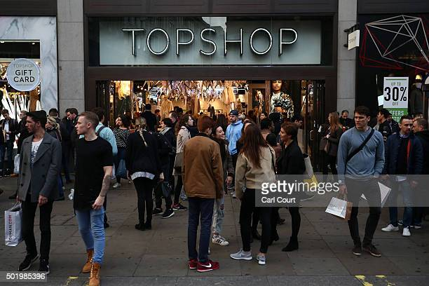 People wait outside a branch of Topshop on Oxford Street on December 19 2015 in London England Shoppers have taken to the high street on the last...