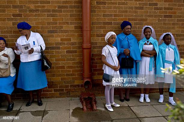People wait outside a church before attending a mass commemorating late South African President Nelson Mandela on December 8 2013 in Soweto near...