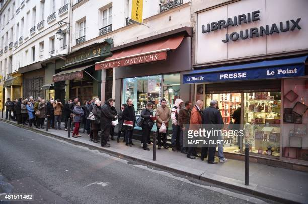 People wait outside a newsagents in Paris on January 14 2015 as the latest edition of French satirical magazine Charlie Hebdo goes on sale The latest...