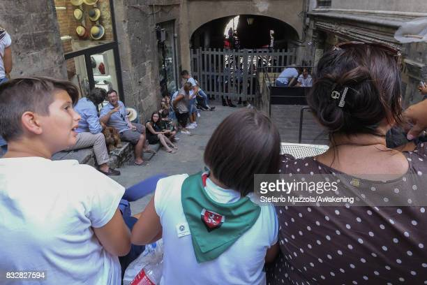 People wait outside Piazza del Campo with the entrances closed ahead of today's Palio on August 16 2017 in Siena Italy The Palio is the most famous...