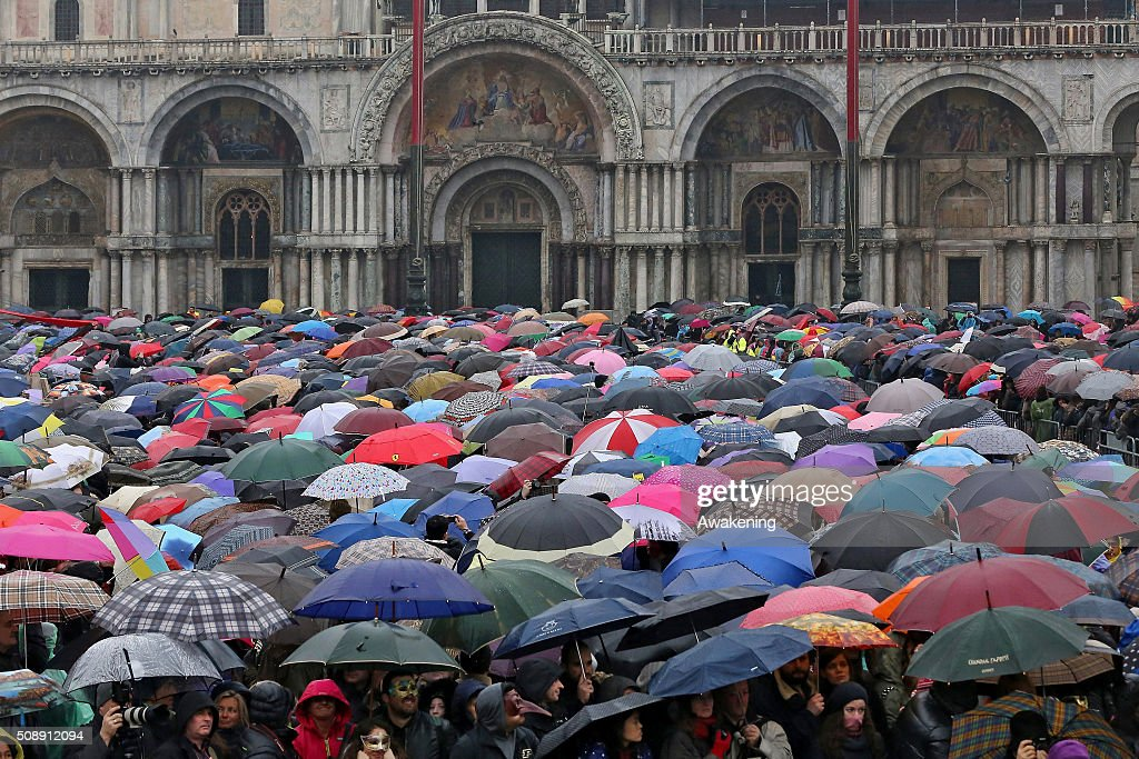 People wait the international bass player Saturnino performance during the 'Volo dell'Aquila', as he flies down from San Marco Tower to the Square at Piazza San Marco on February 7, 2016 in Venice, Italy. The 2016 Carnival of Venice will run until February 9 and includes a program of gala dinners, parades, dances, masked balls and music events.