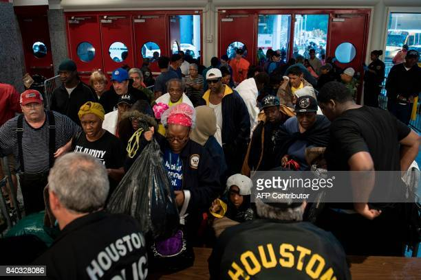 People wait to be checked by police before entering a shelter in the George R Brown Convention Center during the aftermath of Hurricane Harvey on...